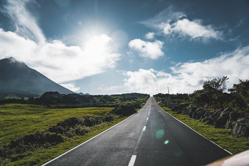 De rechte longitudinale weg van EN3 ten noordoosten van Onderstel Pico en het silhouet van het Onderstel Pico, Pico-eiland, de Az royalty-vrije stock afbeelding