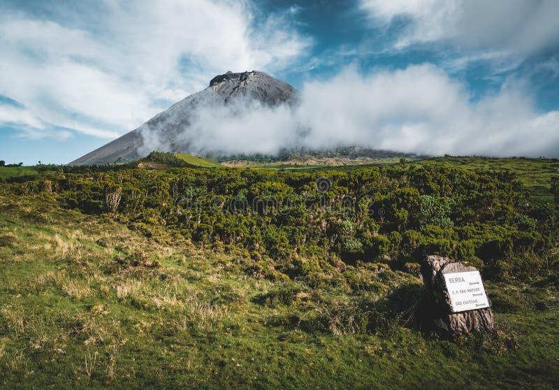 De rechte longitudinale weg van EN3 ten noordoosten van Onderstel Pico en het silhouet van het Onderstel Pico, Pico-eiland, de Az stock afbeelding