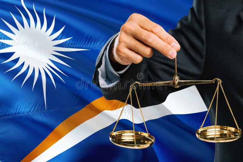 De rechter houdt gouden schalen van rechtvaardigheid met golvende de vlagachtergrond van Marshall Islands Gelijkheidsthema en jur royalty-vrije stock foto