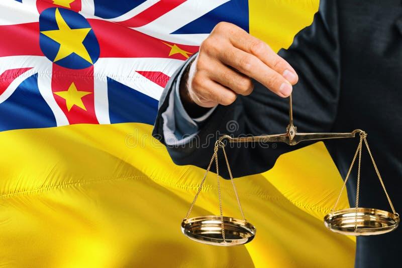 De rechter houdt gouden schalen van rechtvaardigheid met golvende de vlagachtergrond van Niue Gelijkheidsthema en juridisch begri royalty-vrije illustratie
