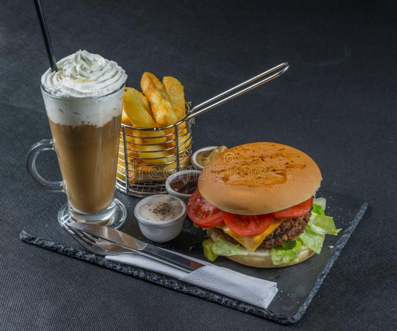 De rechterkantmening over een vlam roosterde dubbele stapelcheeseburger, le royalty-vrije stock afbeelding