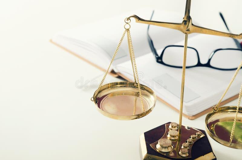 De rechtvaardigheid van de wetsschaal met boek en glazen op achtergrond stock foto