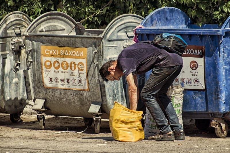 De recyclerende mens knoeit het karton in een zak stock afbeelding