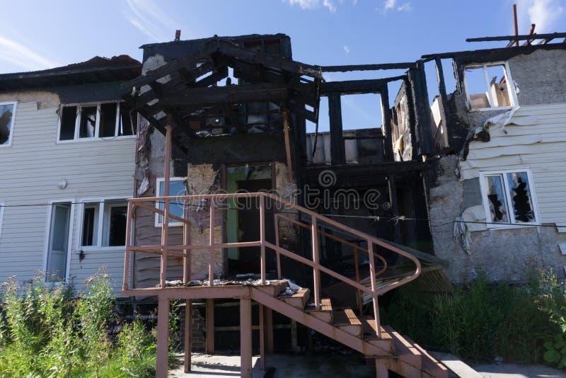 De reddersbrandbestrijders doven een brand op het dak Het gebouw na de brand Gebrand venster Geruïneerd Huis catastrofe Roet  stock afbeelding