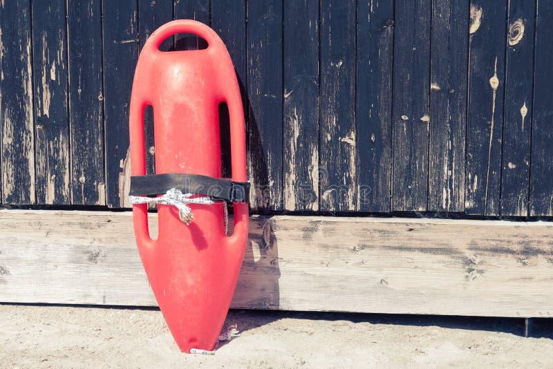 De redding kan op houten bij het strand ommuren stock afbeelding