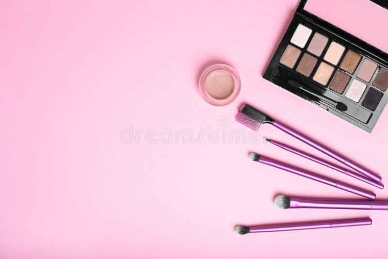 De reeks borstels voor make-up verspreidde zich chaotically op roze achtergrond Professionele make-upborstels en hulpmiddelen Vla stock afbeeldingen