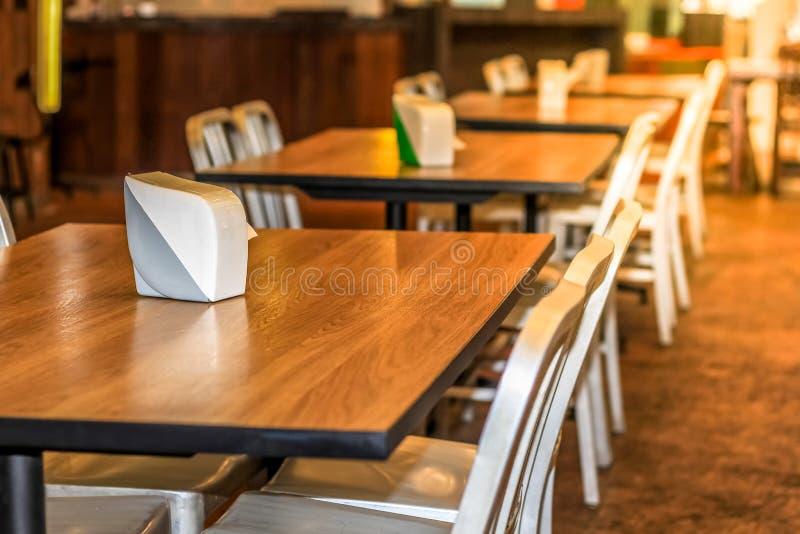 De reeks eettafel, Houten lijstbovenkant en witte stoelen in het hotelrestaurant, verfraait met warm licht stock foto's