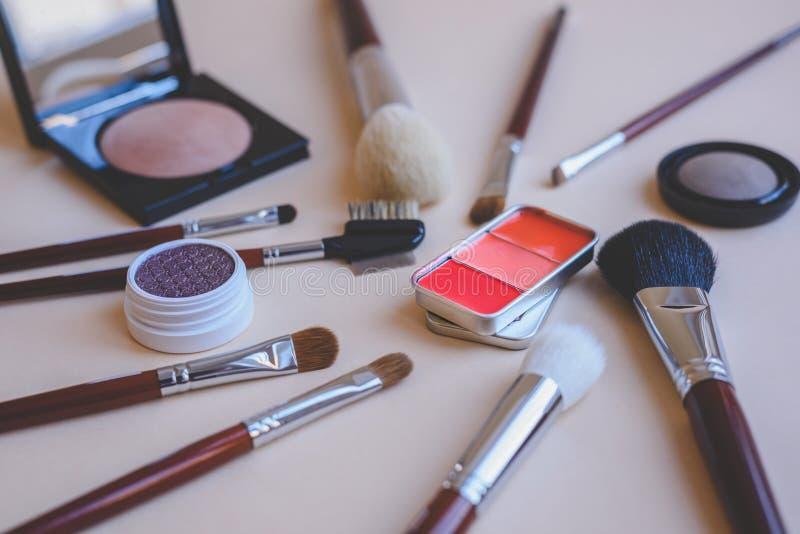De reeks make-upproducten met divers schoonheidsmiddel borstelt een palet van rode lippenstift in een uitstekende oogschaduw van  stock foto's