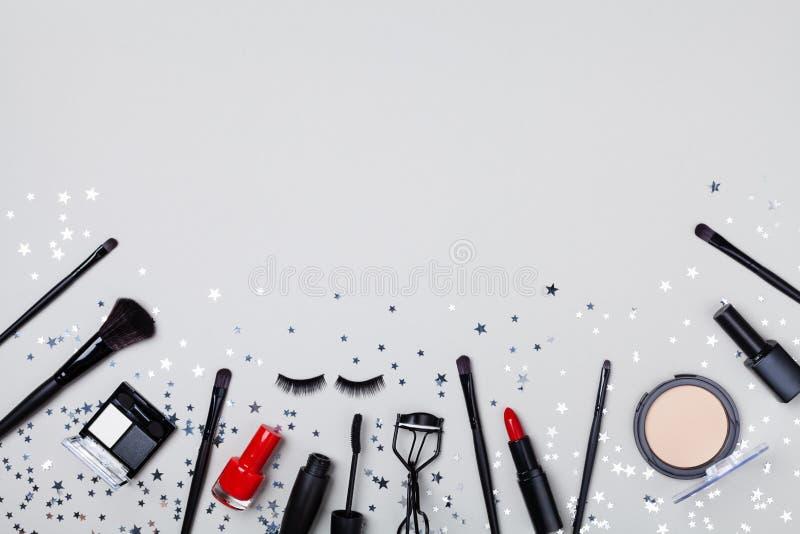 De reeks professionele decoratieve schoonheidsmiddel en make-up verfraaide hulpmiddelen speelt confettien op de grijze mening van stock afbeeldingen