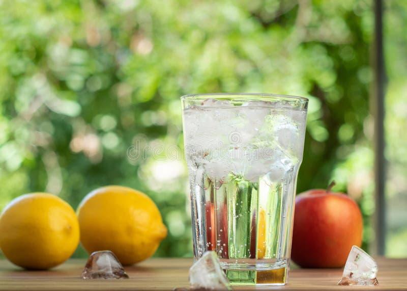 De reeks van glashoogtepunt van water en smeltende ijs en verse vruchten, sluit omhoog mening Citroenen, appel en glas met ijsblo stock foto