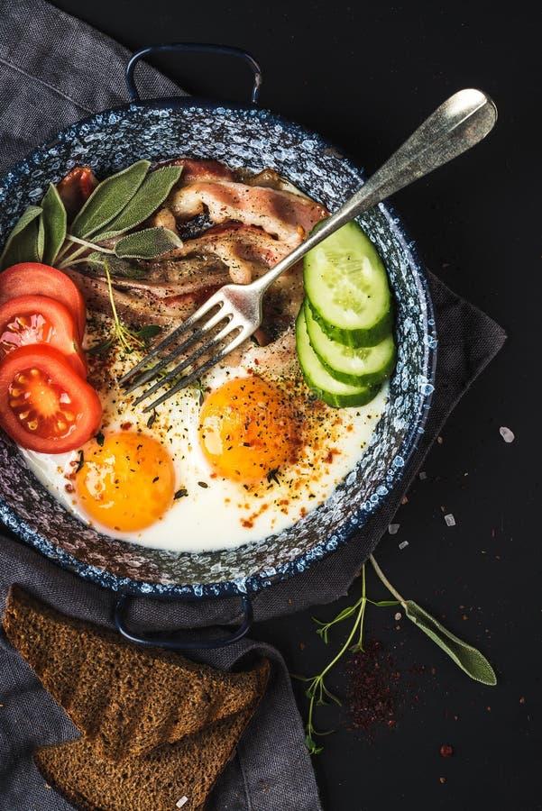 De reeks van het ontbijt Pan van gebraden eieren met bacon, verse tomaat, komkommer, salie en brood op donkere dienende raad over stock afbeelding