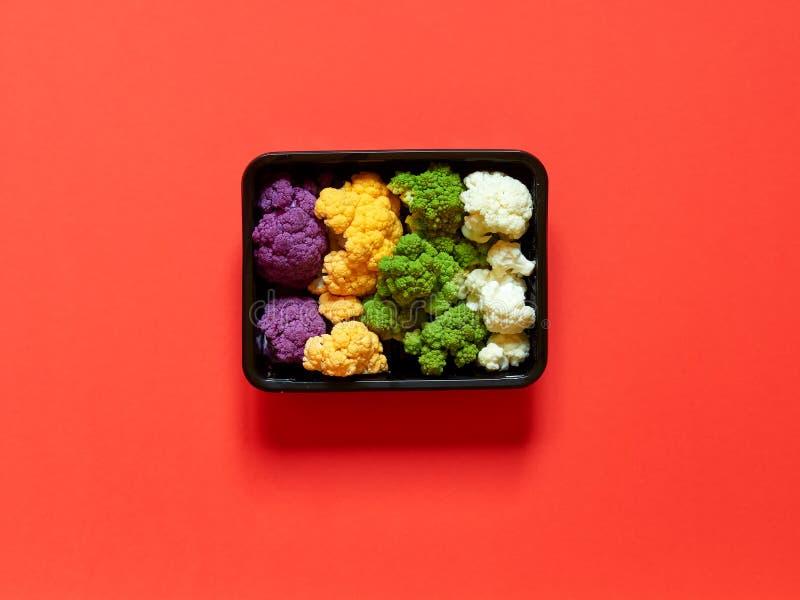 De reeks van kleurrijk bloemkoolviooltje, geel, groen en wit deed - in een plastic ontvanger over een rode achtergrond in dozen royalty-vrije stock afbeelding