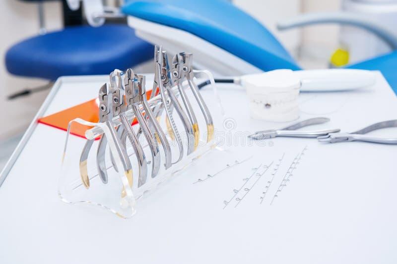 De reeks van OrthodontistDental klemmen en buigtang en andere hulpmiddelen op de het werk lijstoppervlakte stock afbeeldingen