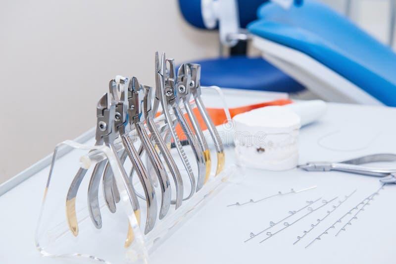 De reeks van OrthodontistDental klemmen en buigtang en andere hulpmiddelen op de het werk lijstoppervlakte stock afbeelding