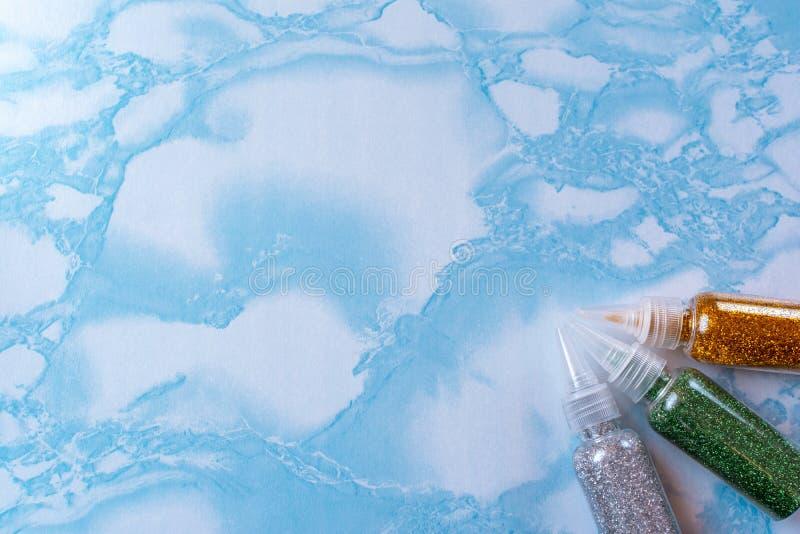 De reeks van smaragd, zilver en goud schittert in plastic flessen voor zeep het maken op de oppervlakte van blauw marmer, omhoog  stock afbeelding