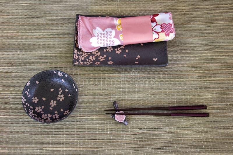De reeks van sushi Twee houten eetstokjes, kleine zwarte die kom op houten achtergrond wordt gediend stock fotografie