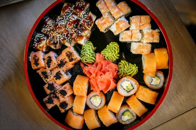 De reeksen van sushinigiri, broodjes en sashimi dienden in traditioneel Japan zwarte Sushioke om plaat stock foto's