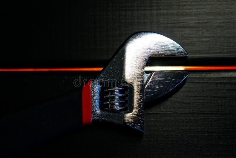 De regelbare moersleutel ligt op een zwarte houten oppervlakte in de workshop Apparaten voor het werk van de werktuigkundige en d stock foto
