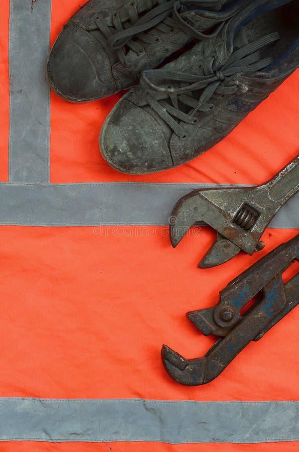 De regelbare moersleutels en de oude laarzen liggen op een oranje overhemd van de signaalarbeider Stilleven verbonden aan reparat royalty-vrije stock afbeeldingen