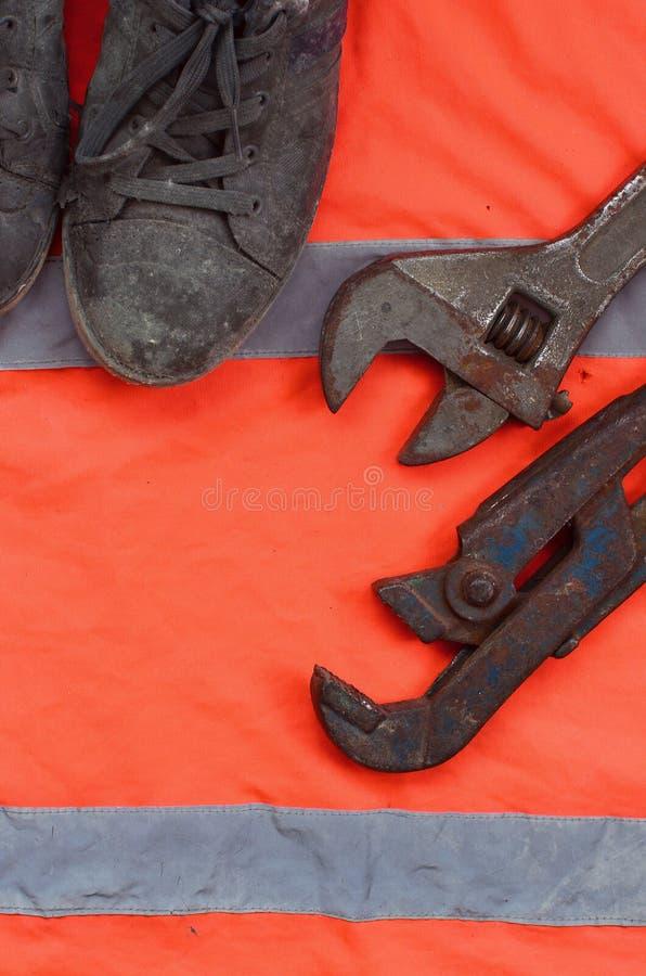De regelbare moersleutels en de oude laarzen liggen op een oranje overhemd van de signaalarbeider Stilleven verbonden aan reparat stock fotografie