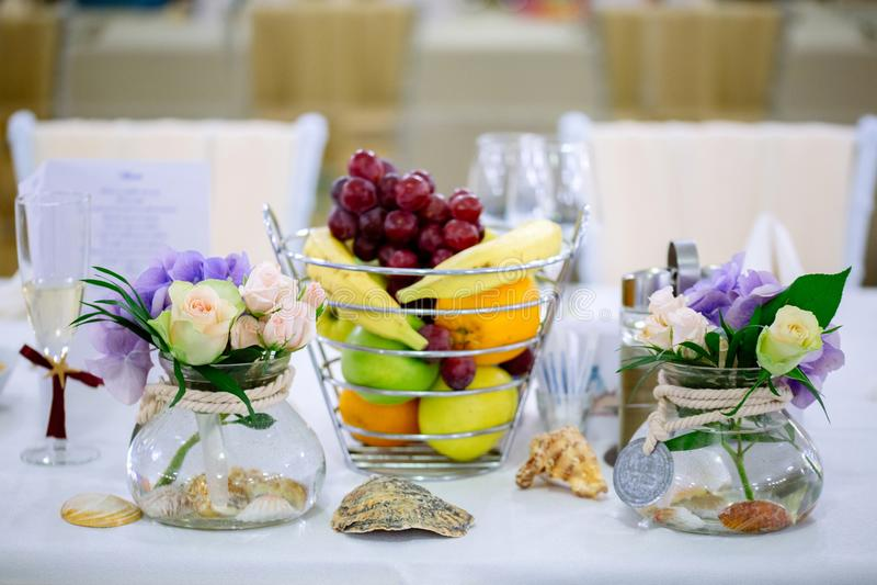 De regeling van de huwelijkslijst met bloemboeketten en fruitmand stock afbeeldingen