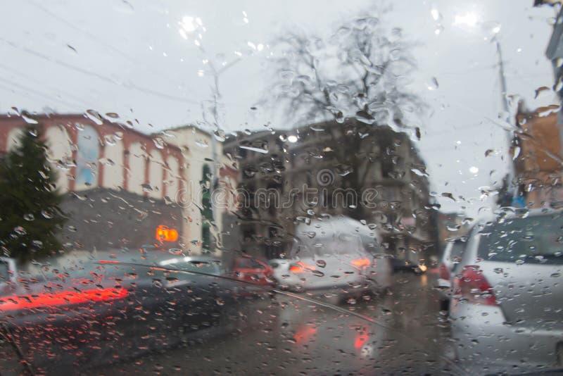 De regenachtige dagen, Avond, regendalingen op het venster met verkeer vertroebelen Onscherp autosilhouet stock fotografie