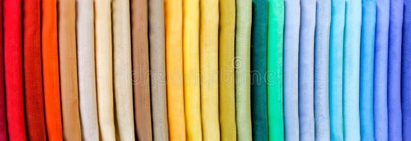 De regenboog kleedt achtergrond Stapel van heldere gevouwen kleren royalty-vrije stock foto