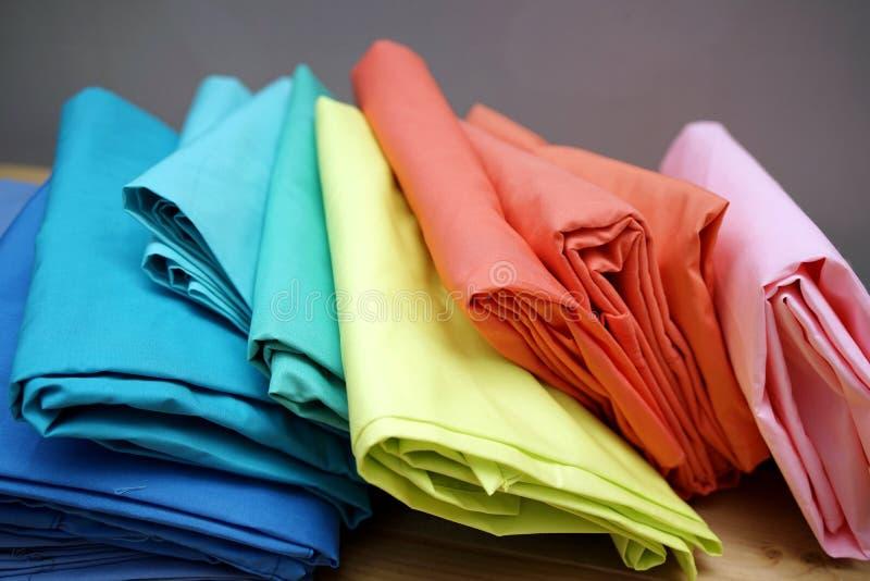 De regenboog kleedt achtergrond Stapel van heldere gevouwen kleren op houten lijst Regenboogwasserij met exemplaarruimte stock fotografie