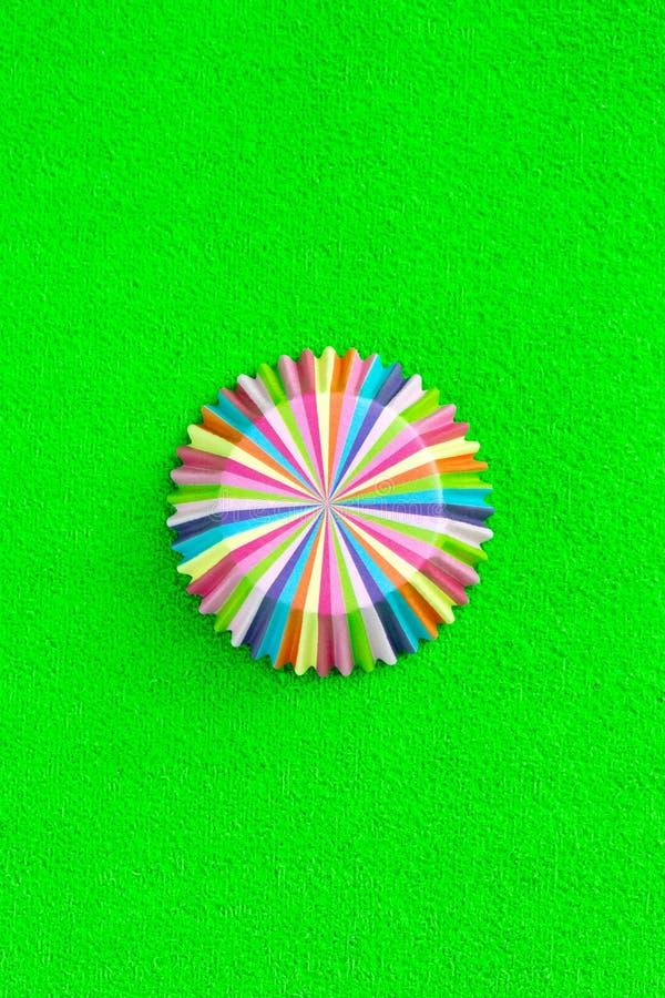 De regenboog kleurde document bakselkoppen voor muffins en cupcakes op een groen minimaal creatief concept als achtergrond Ruimte stock fotografie
