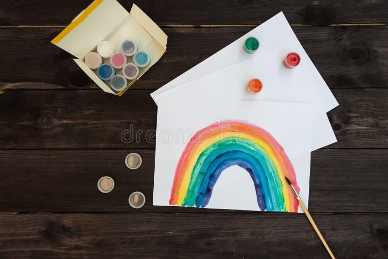 De regenboog met verven wordt geschilderd ligt op een houten lijst die stock afbeeldingen