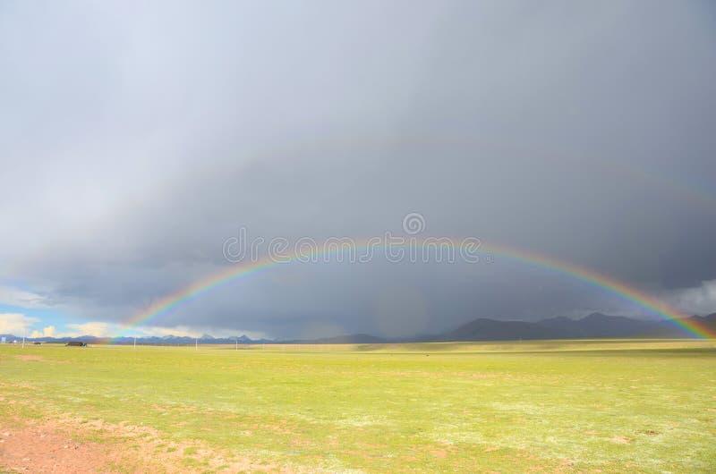 De regenboog onder dark betrekt in Tibet stock afbeeldingen