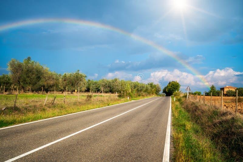 De regenboog over weg en landbouwlandschap stock afbeeldingen