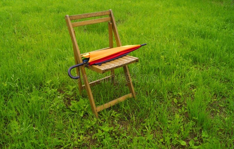 De regenboogparaplu rust op een houten stoel stock fotografie