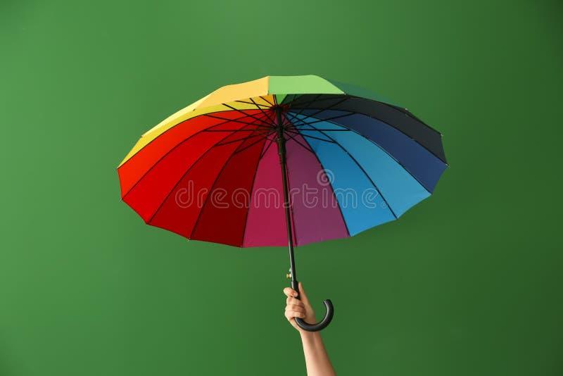 De regenboogparaplu van de vrouwenholding op kleurenachtergrond LGBT-Concept stock afbeelding