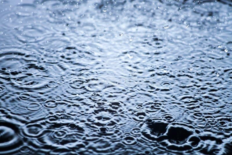 De regendalingen in het water sluiten omhoog, achtergrond stock foto's