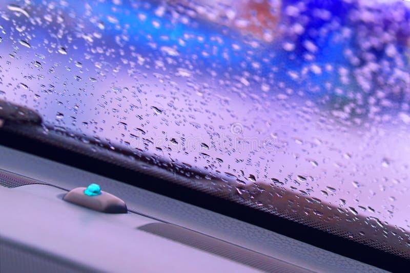 De regendalingen op het voorglas van de vensterauto met een vage violette achtergrond royalty-vrije stock foto's