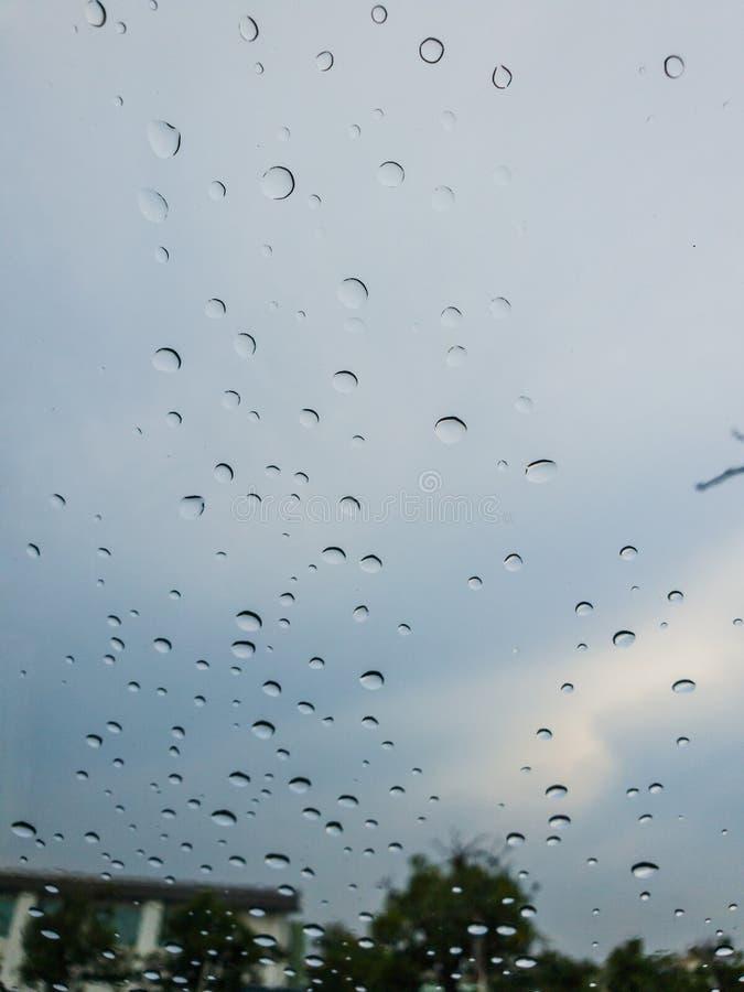 De Regendalingen op de oppervlakte van vensterglazen met blauwe hemelachtergrond Natuurlijk Patroon van regendruppels op hemelach stock afbeeldingen