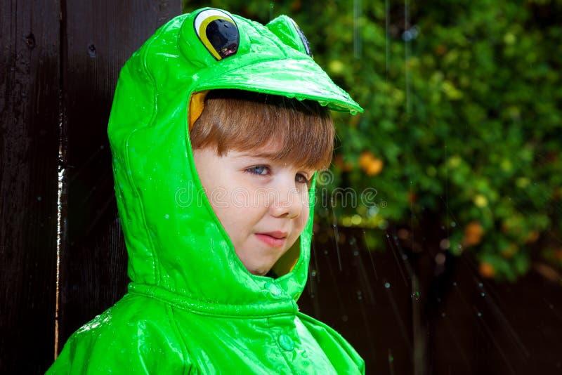 De Regenjas van de jongenskikker met Regen het Bespatten royalty-vrije stock fotografie