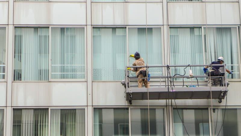 De reinigingsmachine die van het vensterglas buiten het gebouw werken stock foto