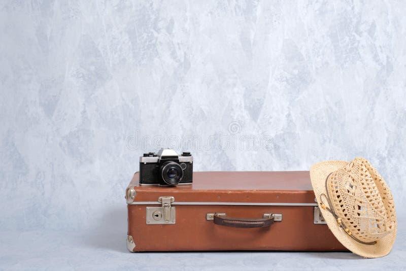 De reis draagt bagage, ouderwetse koffer, strohoed, filmcamera op grijze achtergrond Het concept reis met draagt luggag royalty-vrije stock foto's