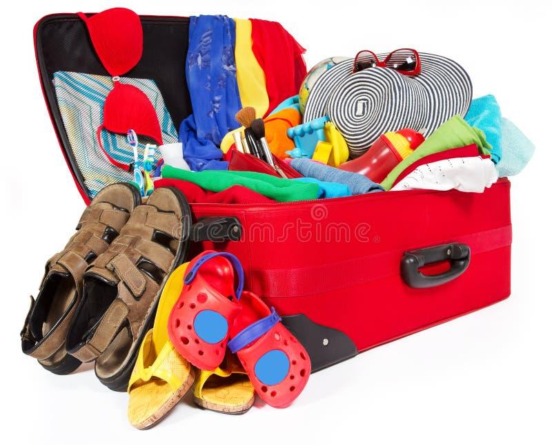 De reis rode koffer van de familie die voor vakantie wordt ingepakt stock afbeeldingen