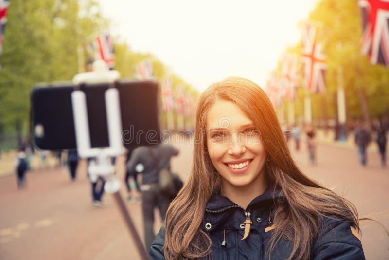 De reis selfie jonge vrouw van Londen Het blije donkerbruine meisje smilling op smartphone stock fotografie