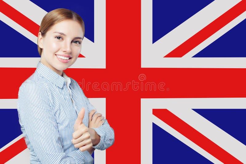 De reis, stage en leert engelstalig in het Verenigd Koninkrijk Mooie studente met duim omhoog tegen de Britse vlagachtergrond royalty-vrije stock foto's