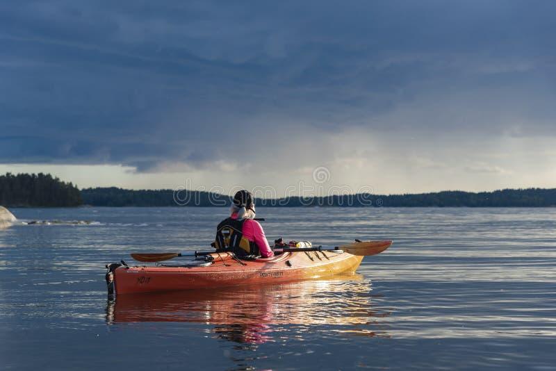 De reizende kayaking vrouw en rainclouds archipel van Stockholm stock afbeelding