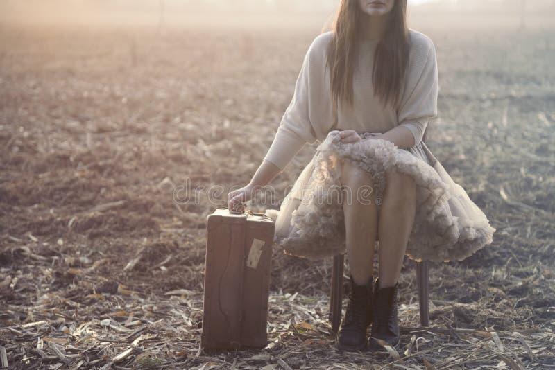 De reizende vrouw gaat zitten om na een lange reis te rusten royalty-vrije stock fotografie