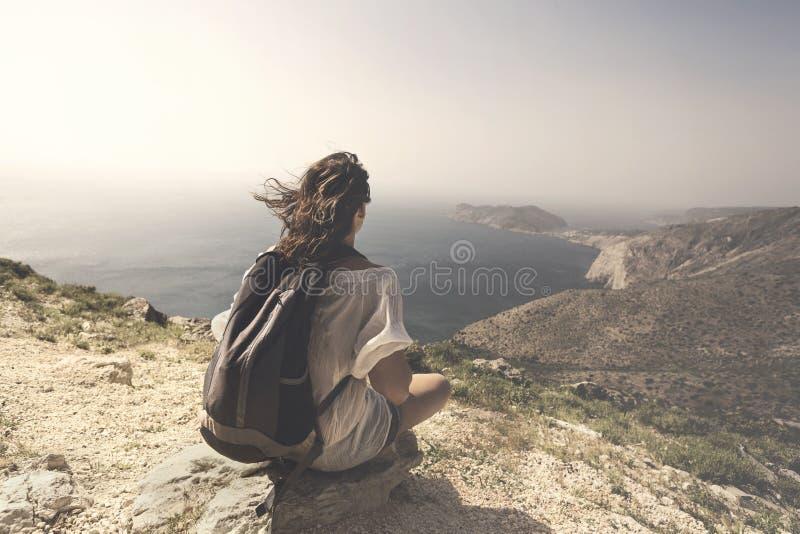 De reizende vrouw ontspant en mediteert op de bovenkant van een berg stock foto