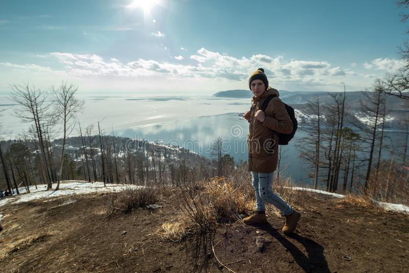 De reiziger bevindt zich op een berg en bekijkt de mooie mening van meer Baikal Het landschap van de winter stock foto's