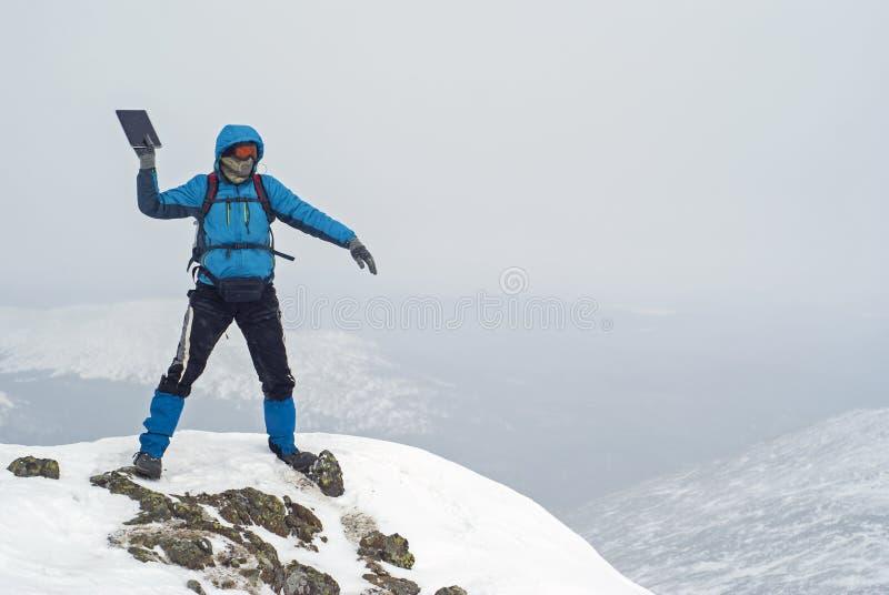 De reiziger boven op een berg werpt laptop in het kloof stock foto's