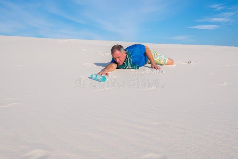 De reiziger die aan dorst lijden, kruipt door de woestijn stock afbeelding