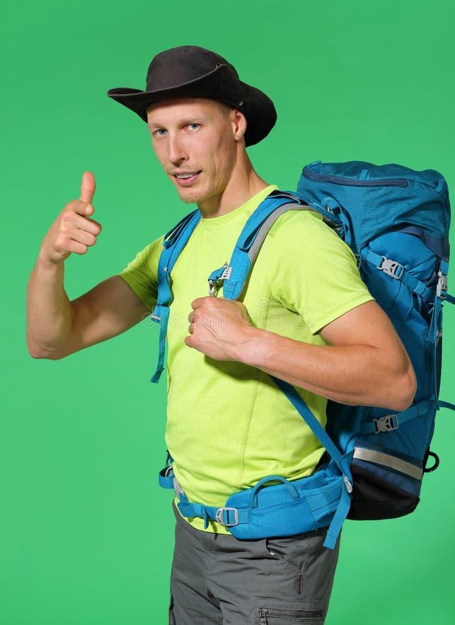 De reiziger in hoed en rugzak het tonen beduimelt omhoog Chromakeyachtergrond royalty-vrije stock afbeelding